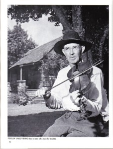 "Caption: ""FIDDLIN' JAKE VINING liked to saw off a tune for tourists."" That looks like Uncle Matt's Cabin in the background. Date Taken: Place Taken: Branson, Missouri"